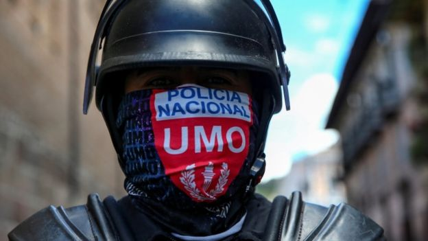 A member of the national police wears a face covering during protests in Quito
