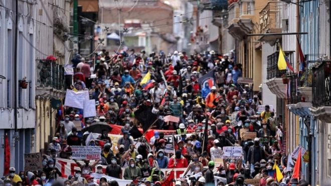 Thousands of protesters march through the streets of Quito